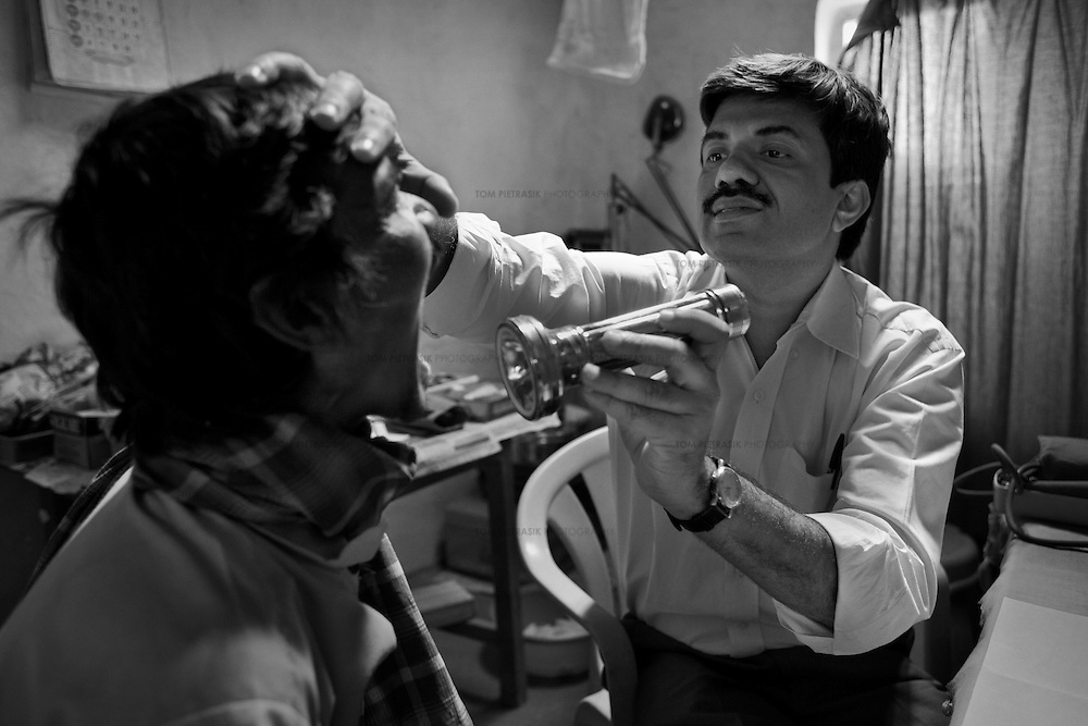 Dr. Yogesh Jain examines a patient during a weekly out-patient clinic at the JSS outreach medical centre in Bamhni village.<br /> <br /> The JSS (Jan Swasthya Sahyog or People's Health Support Group) is a public-health initiative established in 1996 by a handful of committed doctors, all of whom trained at elite medical schools in India. While many of their peers secured high profile, high earning posts in premier hospitals in India, the US and the UK, the doctors at JSS provide a service for poor and marginalised rural communities in Bilaspur district in the eastern India.<br /> <br /> The JSS operate out of a hospital in Ganiyari, near Bilaspur. Relying on grants and donations, the JSS provide a first-class service for a community that would otherwise rely on underfunded and poorly resourced government facilities. Though JSS hospital boasts 30 beds, two operating theatres, a fully-equipped lab and three outpatient clinics a week, the service provided by JSS is over-subscribed by a community of 800,000 people from 1,500 villages. <br /> <br /> To address the malnutrition, the JSS offers training on new agricultural techniques. The JSS has a well established outreach program of village-clinics and employs over 100 village health workers serving 53 villages. They also operate an ambulance service and assist with transport costs for a community who's access to essential services has been undermined by the Chhattisgarh government's decision to completely disinvest in public transport. <br /> <br /> Continually exposed to illnesses associated with malnutrition and poverty including tuberculosis and rheumatic heart disease, the doctors at JSS are tireless advocates for universal healthcare and focus resources upon the three-quarters of India's population (over 800 million people) who live on less than 20 Rupees (50 US cents) a day. <br /> <br /> Photo: Tom Pietrasik<br /> Chhattisgarh, India. <br /> March 2010