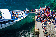 Tour boat and tourists at crowded dock, Vernazza, Cinque Terre, Liguria, Italy
