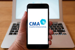 Using iPhone smartphone to display logo of the CMA, Competition & Markets Authority in the UK