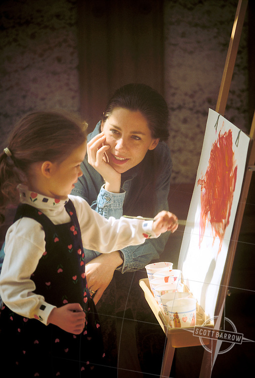 Mother teaching daughter to paint