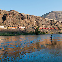 &copy;Ryan Brennecke / 2014<br /> **Edited File<br /> Angler Troy B. Jordan swings his fly through a run as on train passes while fishing the lower Deschutes River for steelhead.