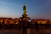 "Crowds are passing and photographing the statue of  ""John of Nepomuk"" which is an outdoor sculpture, installed in 1683 on the north side of the Charles Bridge in Prague, Czech Republic."