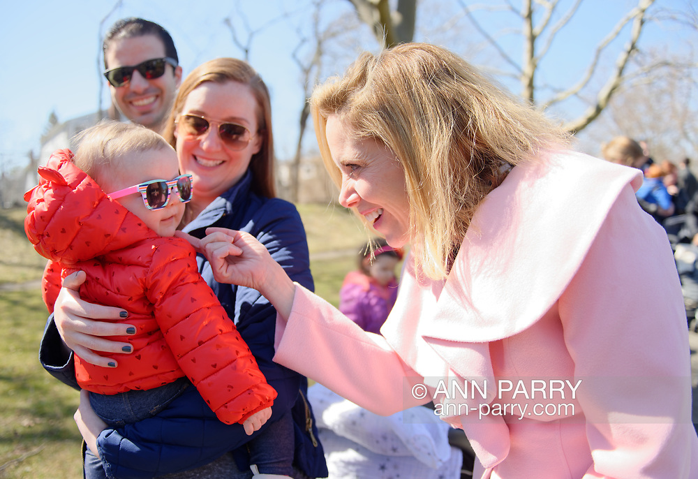 North Merrick, New York, USA. March 31, 2018. At right, Town of Hempstead Supervisor LAURA GILLEN chucks 8-month-old EMMA HALPERN under the chin, who is held by her mom KELLY HALPERN, with dad MATT HALPERN looking on, at the Annual Eggstravaganza, with Easter Egg Hunt, held at Fraser Park and hosted by North and Central Merrick Civic Association (NCMCA) and Merrick's American Legion Auxiliary Unit 1282. Halpern family is from Merrick.