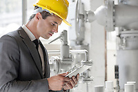 Young male supervisor using tablet PC in industry