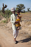 Indian Bishnoi man carrying grandchild near Rohet in Rajasthan, Northern India
