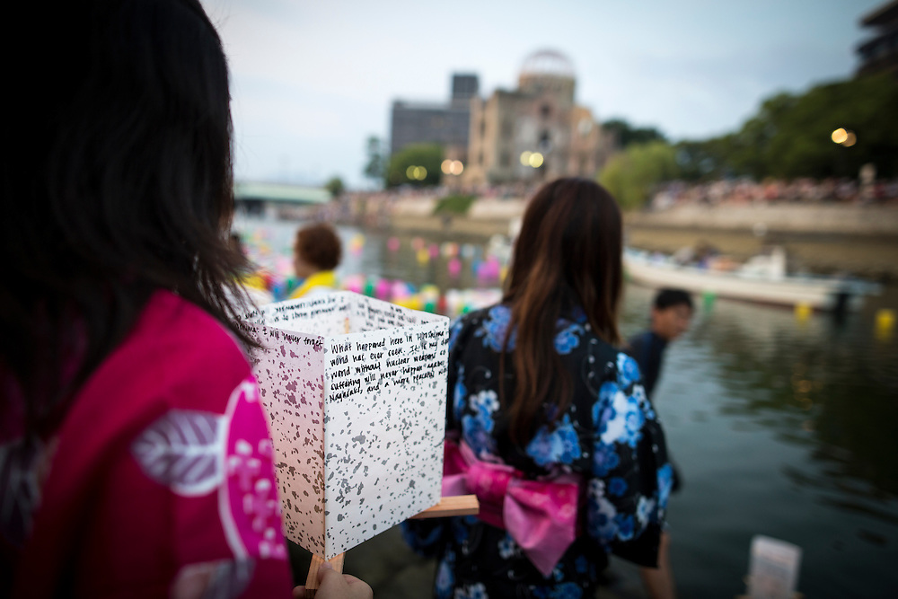HIROSHIMA, JAPAN - AUGUST 6 : Women wait to float candle lit lanterns with their written message on the Motoyasu River during the 71st anniversary activities, commemorating the atomic bombing of Hiroshima at the Hiroshima Peace Memorial Park on August 6, 2016 in Hiroshima, western Japan. Japan marks the 71st anniversary of the first atomic bomb that was dropped by the United States on Hiroshima on August 6, 1945 during World War II.  (Photo by Richard Atrero de Guzman/NURPhoto)
