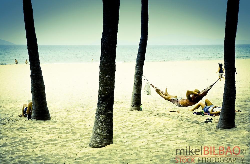 people resting on a hammock. Cua Dai beach. <br /> Hoi An, Vietnam, Asia.
