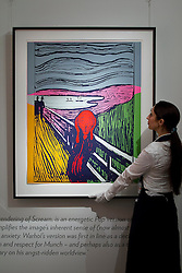 © Licensed to London News Pictures. 14/09/2012. LONDON, UK. A member of Sotheby's staff adjusts Andy Warhol's 'The Scream (After Munch)' (1984) est. £2000,000-3000,000 as the New Bond Street auction house prepares for a sale of 'Old Master, Modern and Contemporary Prints'. The auction, set to take place on the 19th of September 2012, features nearly 200 masterful works artists including Andy Warhol, Lucian Freud and Francis Bacon. Photo credit: Matt Cetti-Roberts/LNP