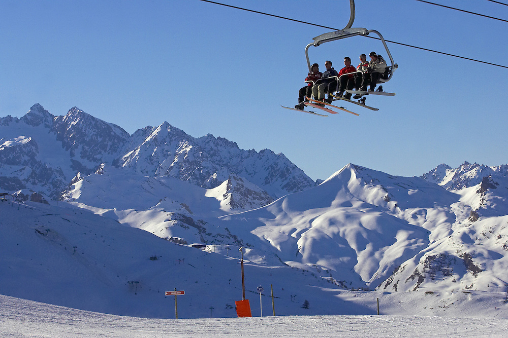 A group of skiers and snowboarders on a six man chairlift in Serre Chevalier, France