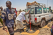 A World Food Programme team works to free their vehicle from wet sand encountered during a river crossing.