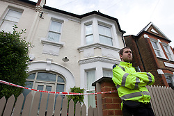 © licensed to London News Pictures. London, UK 10/05/2012. A police officers waiting outside the house where a 10-week-old boy and his 14-month-old sister were found dead by police in Killarney Road, Wandsworth, south-west London. Photo credit: Tolga Akmen/LNP
