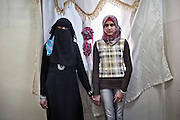 Layla and Sama are 13 and 15 years old. Their mother, Um Muhammad, 39, says life is hard without her fighter husband. The mother of six is struggling to secure the monthly rent, is under constant pressure to marry off her daughters to Jordanian and Syrian suitors...Layla, right, was trampled upon in her sleep when an army unit stormed their house looking for their father before they fled to Jordan. 2013