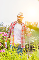 Portrait of mature gardener standing while holding fork rake