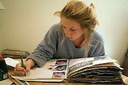 Model released image of teenage girl working on her art folder