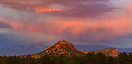 Stormy sunset sky over the Mesa at Otowi Ruin, with the Sangre de Cristo Mountains in the background. The Otowi Ruin is now mounds of the fallen stone walls overgrown with grass, creating the meadow area at the lower left. © 2017 David A. Ponton