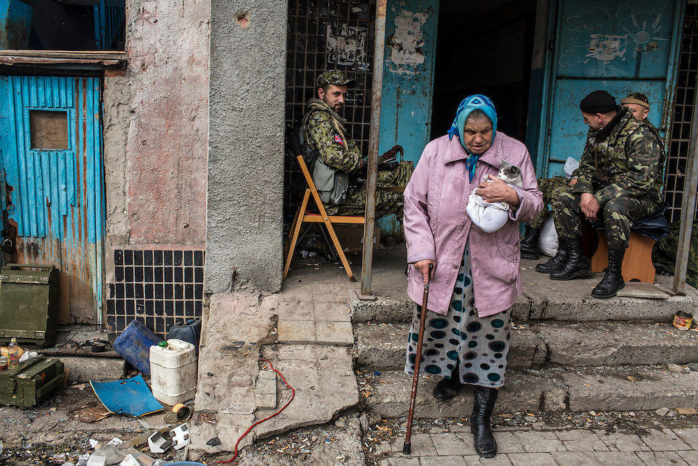 Nadezda Panasyk, 75, walks with her cat Pushok (Fluffy) past pro-Russian rebels outside her apartment building in the Kievsky district where she lives on Friday, October 17, 2014 in Donetsk, Ukraine. Her building is used by fighters for the Donetsk People's Republic to coordinate efforts to gain control of the Donetsk airport, one of the most heavily contested ongoing battles of the war in Eastern Ukraine. Photo by Brendan Hoffman, Freelance
