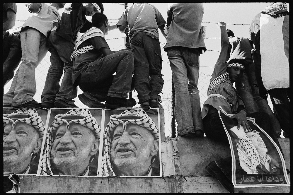 Palestinians try to catch a glimpse of Arafat's burial in the Al-Muqataa compound in Ramallah.