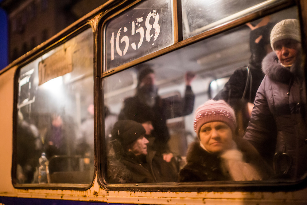 DONETSK, UKRAINE - JANUARY 24, 2015: A woman looks out the window of a trolleybus as it passes a memorial event for victims at the site of a rocket strike that hit a trolleybus two days earlier in Donetsk, Ukraine. The attack killed at least eight civilians and injured many more. CREDIT: Brendan Hoffman for The New York Times