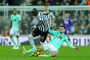 Lewis Cook (#16) of Bournemouth lunges in from behind, fouling Mohamed Diame (#10) of Newcastle United during the Premier League match between Newcastle United and Bournemouth at St. James's Park, Newcastle, England on 10 November 2018.