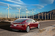 rear view of Red 2015 Tesla Model S P85+ photographed amongst the power generating windmills of Palm Springs, CA