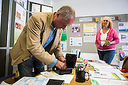 Inside the Wadebridge Renewable Energy Network (WREN) energy shop in Wadebridge, North Cornwall, United Kingdom. The shop is the focal point for WRENs activities which aims to turn the area into the first renewable energy town.  A British man gets WREN currency money out of a money box for a local woman.