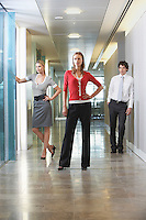 Three businesspeople standing in office corridor portrait