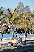 A surfer walks to Ipanema beach for early morning surf with Two Brothers Mountain in Rio de Janeiro, Brazil.