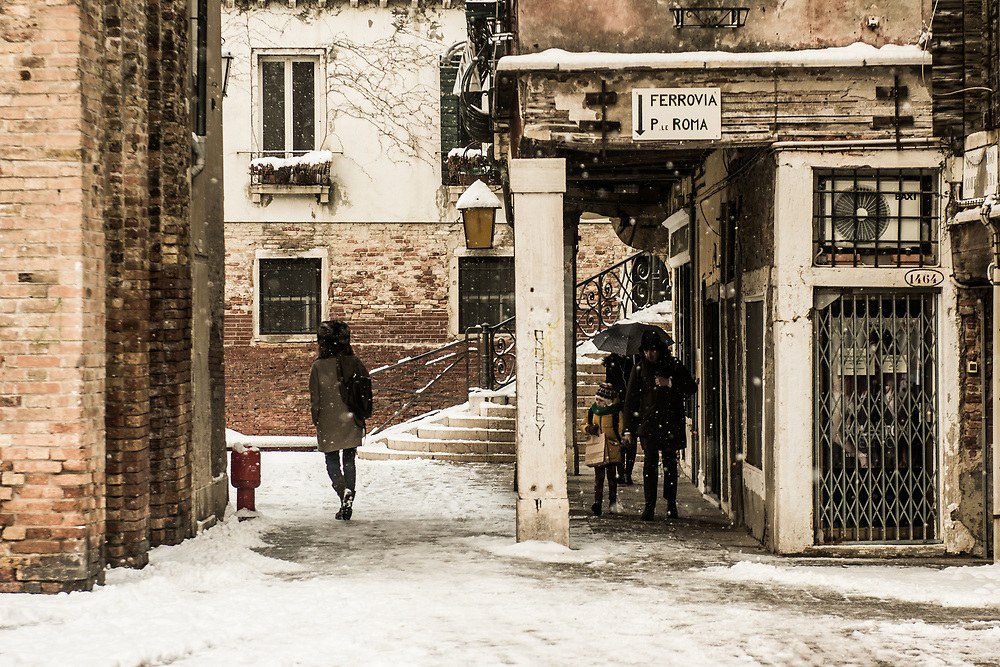 VENICE, ITALY - 28th FEBRUARY/01st MARCH 2018<br /> People walk under a portico to protect themselves by the snowfall in Venice, Italy. A blast of freezing weather called the &ldquo;Beast from the East&rdquo; has gripped most of Europe in the middle of winter of 2018, and in Venice A snowfall has covered the city with white, making it fascinating and poetic for citizen and tourists.   &copy; Simone Padovani / Awakening