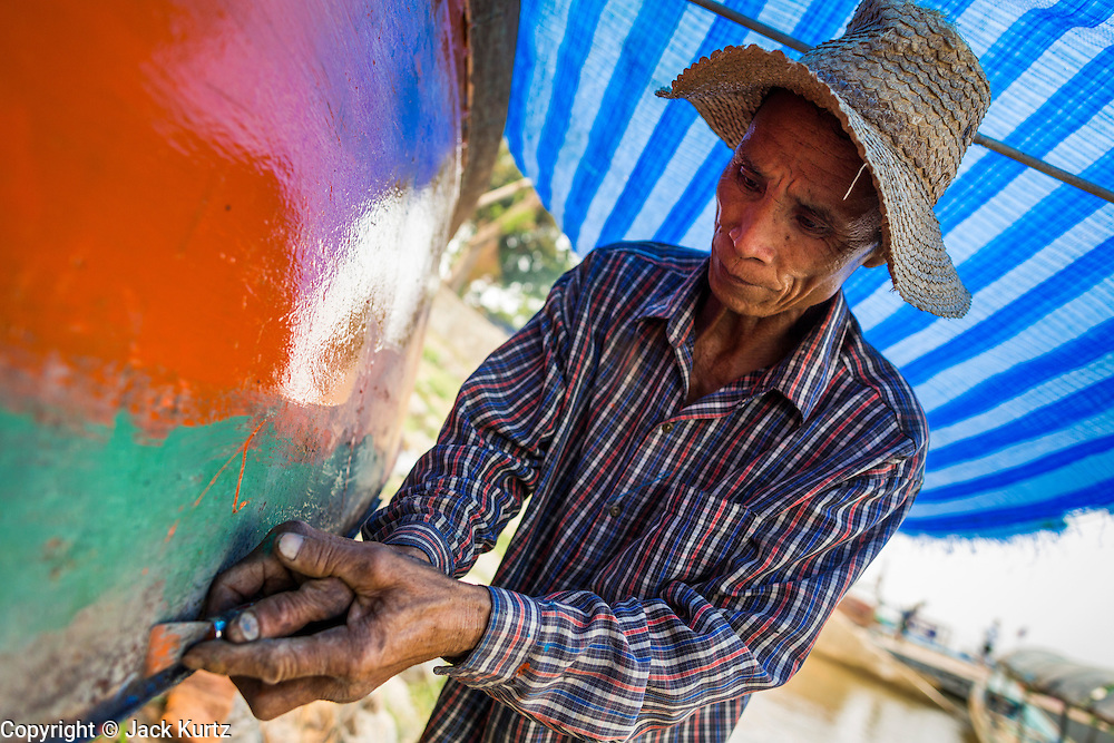 21 APRIL 2014 - CHIANG SAEN, CHIANG RAI, THAILAND: A man works on a small river freighter on the beach in Chiang Saen, Thailand. Chiang Rai province in northern Thailand is facing a drought this year. The 2014 drought has been brought on by lower than normal dry season rains. At the same time, closing dams in Yunnan province of China has caused the level of the Mekong River to drop suddenly exposing rocks and sandbars in the normally navigable Mekong River. Changes in the Mekong's levels means commercial shipping can't progress past Chiang Saen. Dozens of ships are tied up in the port area along the city's waterfront.      PHOTO BY JACK KURTZ