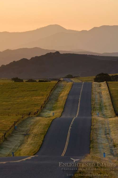 Golden sunrise light over long straight two lane country road and rolling hills in Spring, Santa Ynez Valley, California