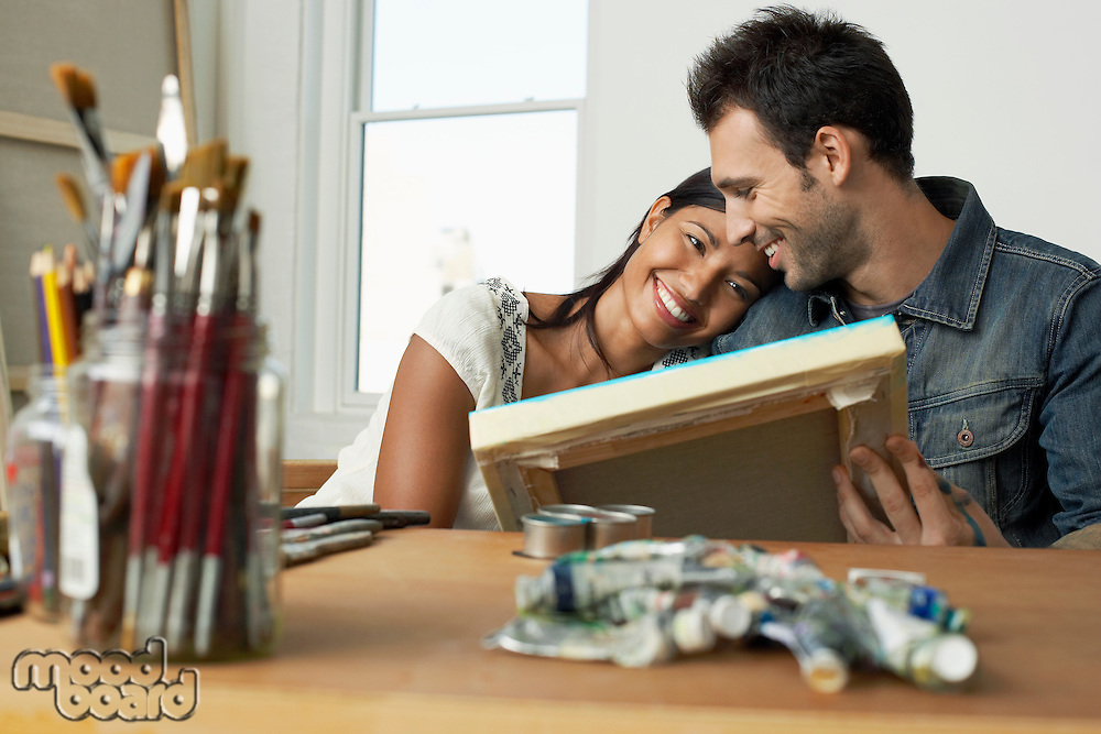 Couple looking at painting in artist studio