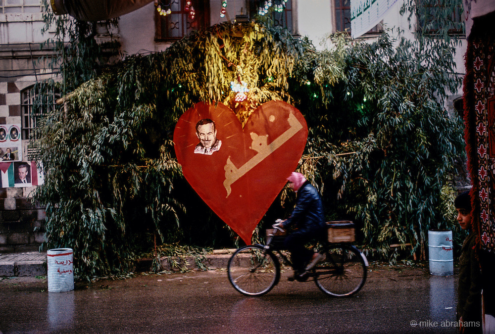 'PERSONALITY CULT OF ASSAD', CYCLIST PASSING BUILDING WITH LARGE HEART & PHOTO OF ASSAD OUTSIDE DURING THE REFERENDUM CAMPAIGN, DAMASCUS, DECEMBER 1991.