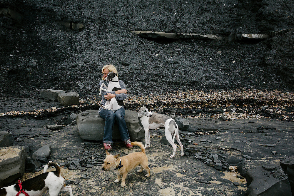 A local woman spends the day out searching for fossils by the sea cliffs with her dogs. The area is noted for the fossils found in the cliffs and beaches, which are part of the Heritage Coast—known commercially as the Jurassic Coast—a World Heritage Site.