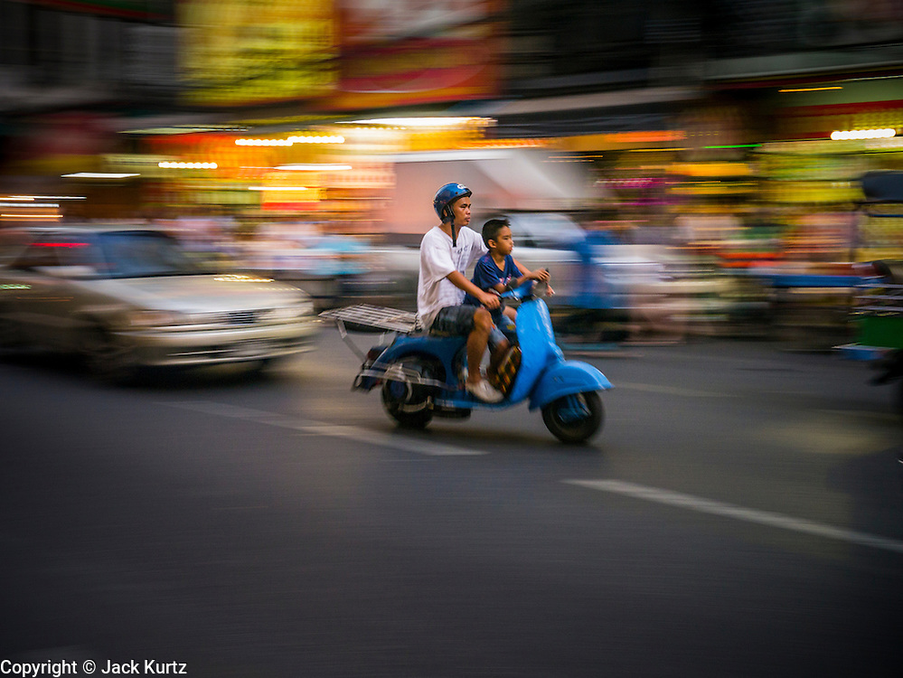 29 DECEMBER 2012 - BANGKOK, THAILAND: People on a motorscooter on Yaowarat Road in Samphanthawong district in the Chinatown area of Bangkok, Thailand.       PHOTO BY JACK KURTZ