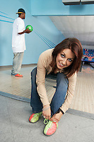 Young Woman Tying Bowling Shoes