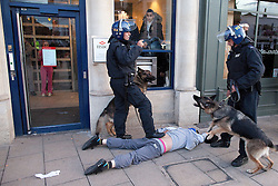 © Licensed to London News Pictures. 07/08/2011. Enfield, UK. Police men and a police dog detain a man. Police engage in a tense standoff with youths in Enfield Town Centre. They stop and search some. A police car and local shops have been vandalised. Groups of masked youths hang around the area. Police dogs are deployed. Photo credit : Joel Goodman/LNP