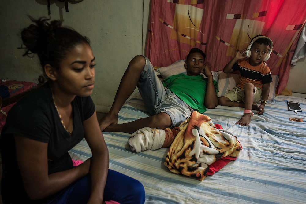 """LA VELA, VENEZUELA - SEPTEMBER 25, 2016: Roger Bello takes care of his nephew, Javier. Javier is staying with Roger and Maria, his grandmother, because his mother, Roymar Bello left to work illegally in Aruba after being deported from Curacao. Roger's 19-year-old girlfriend Yaisbel (left) is six months pregnant. He plans to also pay smugglers to take him to Curacao so that he can earn enough money to provide for his future child. Yaisbel said she would stay behind but take a loan from smugglers to pay for Roger's journey, using her mother's house as collateral. Hopefully, she said, her mother would never find out.  """"I am just watching her stomach,"""" said Roger Bello. """"Before the child is here, I will be in Curaçao."""" PHOTO: Meridith Kohut for The New York Times"""