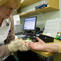 Nurse taking a blood sample from patient's finger<br />