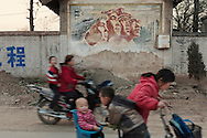 On a street of Beiding village (Yicheng County), parents are bringing their children back home, passing by a propaganda mural painting dating back from the Cultural revolution. In Beiding as in the rest of Yicheng County,  families with a rural hukou (Chinese kind of identity paper) can have as many as two children, a relaxed version of the one child rule that applies elsewhere in China.