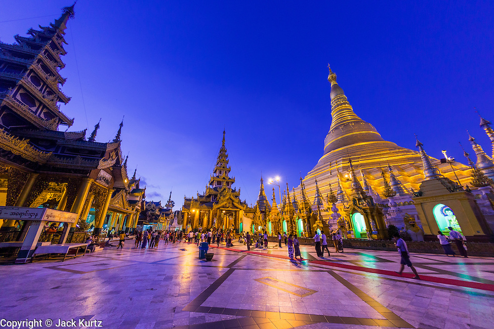 15 JUNE 2013 - YANGON, MYANMAR: Shwedagon Pagoda in the evening. Shwedagon Pagoda is officially known as Shwedagon Zedi Daw and is also called the Great Dagon Pagoda or the Golden Pagoda. It is a 99 meter (325 ft) tall pagoda and stupa located in Yangon, Burma. The pagoda lies to the west of on Singuttara Hill, and dominates the skyline of the city. It is the most sacred Buddhist pagoda in Myanmar and contains relics of the past four Buddhas enshrined: the staff of Kakusandha, the water filter of Koṇāgamana, a piece of the robe of Kassapa and eight strands of hair from Gautama, the historical Buddha. Burmese believe the pagoda was established as early ca 540BC, but archaeological suggests it was built between the 6th and 10th centuries. The pagoda has been renovated numerous times through the centuries. Millions of Burmese and tens of thousands of tourists visit the pagoda every year, which is the most visited site in Yangon.  PHOTO BY JACK KURTZ