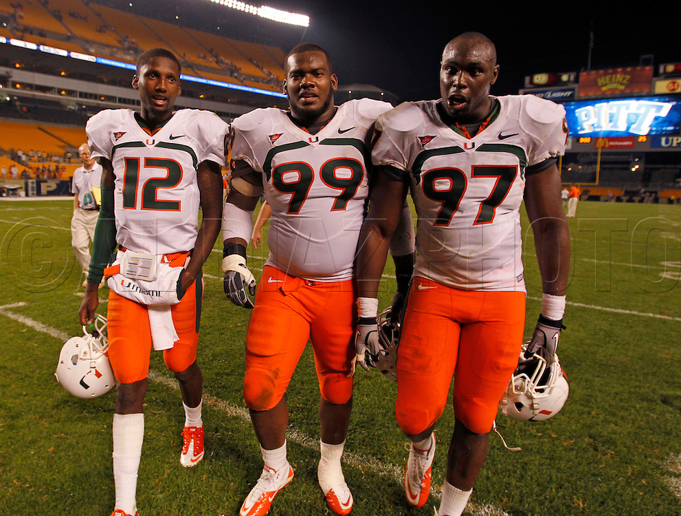 Miami Hurricanes quarterback Jacory Harris (12), defensive lineman Marcus Forston (99) and defensive lineman Adewale Ojomo (97) walk off the field after defeating the Panthers 31-3. The University of Miami  vs The University of Pittsburgh Panthers at Heinz Field in Pittsburgh, PA, on Thursday, September 23, 2010.