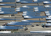 Arkansas Democrat-Gazette/BENJAMIN KRAIN --11/12/2014--<br /> Trucks prepare to haul some of the 1000's of wind turbine blades sitting on the manufacturing lot at the LM Glasfiber plant at the Port of Little Rock. The 150-foot long wind mill blades are made in the Little Rock plant and transported across the country to wind power installations.