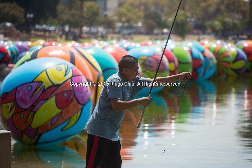 A man fishs as the hand-painted vinyl balls floating in the MacArthur Park Lake as part of a large-scale public arts installation organized by the Portraits of Hope charity in Los Angeles, California on August 26, 2015. The work titled ``The Spheres at MacArthur Park,'' involves filling the park's 8.39-acre lake with about 3,000 balls, each 4 to 6 feet in diameter and covered in bright floral and fish patterns.(Photo by Ringo Chiu/PHOTOFORMULA.com)