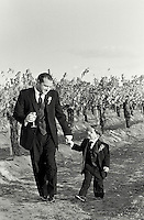 father and son in tux walk through vineyards in temecula wine country wearing a tux. could be groom and ringbearer.