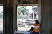 A woman tourist covers her arms with additional sleeves to adhere to the Theravada Buddhist dress code whilst sitting on a stone window ledge in Angkor Wat Siem Reap, Cambodia.  Angkor Wat is Cambodia's main tourist destination and one of UNESCO's world heritage sites. (photo by Andrew Aitchison / In pictures via Getty Images)