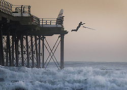 © Licensed to London News Pictures. <br /> 03/10/2016. <br /> Saltburn-by-the-Sea, UK.  <br /> <br /> A surfer leaps from the pier to avoid whitewater breaking against the beach as he goes for a morning surf on a cold October morning at Saltburn-by-the-Sea.<br /> <br /> Photo credit: Ian Forsyth/LNP