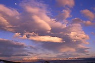 The moon watches over afternoon clouds form over Mono Lake and the snow capped Esatern Sierra Mountains.