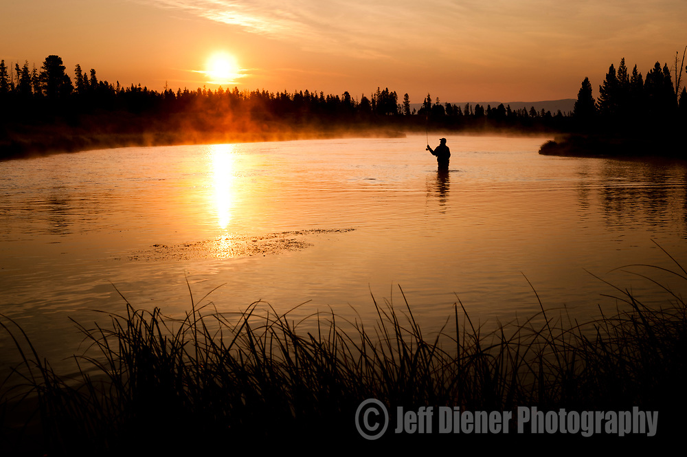 A fly fisherman casts at sunrise while fishing in Wyoming.