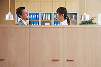Two office workers talking behind cubicle
