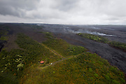 Big Island. Helicopter flight over Hawai'i Volcanoes National Park, in an Eurocopter AS350 Ecureuil (AStar). The lava flow of Kilauaea's Pu'u O'o Crater, active since 1983. Lone house spared by the flow, only accessible by helicopter.